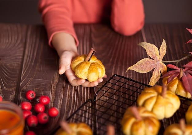 Тыквенные булочки на решетке для выпечки. осенняя концепция. девочка берет одну булочку.
