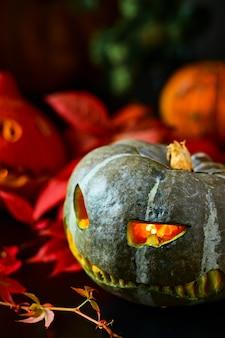 Сжигание тыквы на деревянном и собранные тыквы разложены на старом столе и украшены ивовыми листьями, осенними овощами.