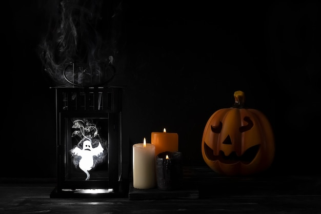 Pumpkin, candles and ghost in a lantern on black background, restless spirit in the fog, halloween concept, autumn holiday.
