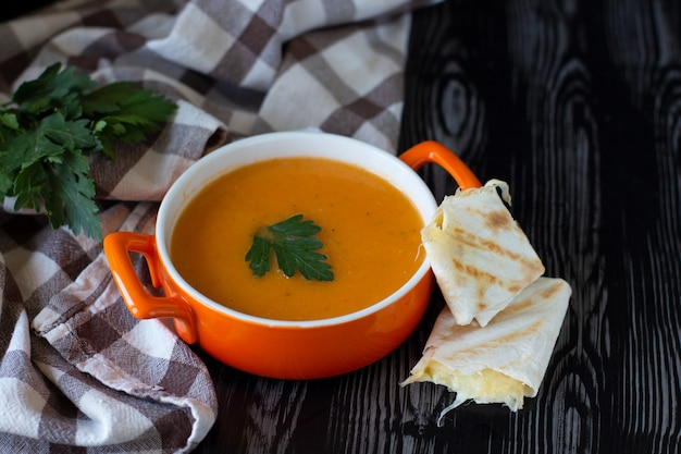 Pumpkin carrot cream soup in an orange plate with cheese pita on a checkered tablecloth