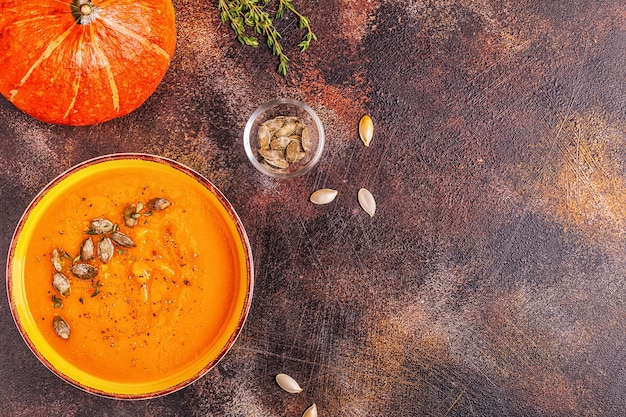 Pumpkin and carrot soup served with seeds, top view.