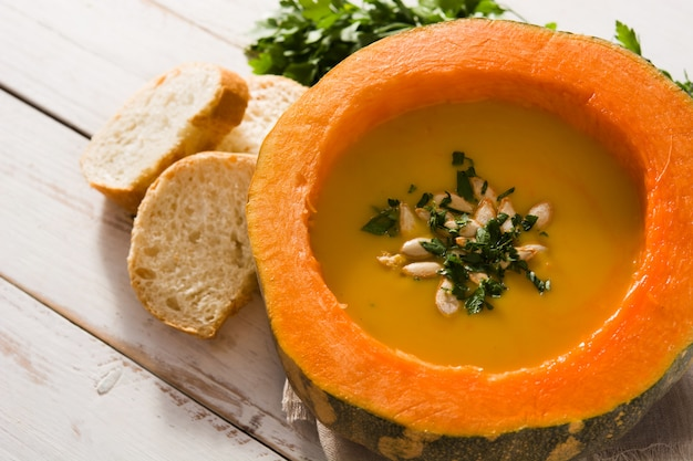 Pumpkin and carrot soup on white wooden table. autumn food.