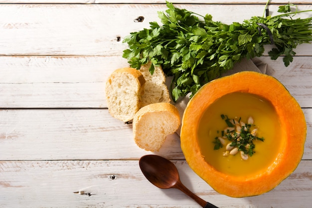 Pumpkin and carrot soup on white wooden table.