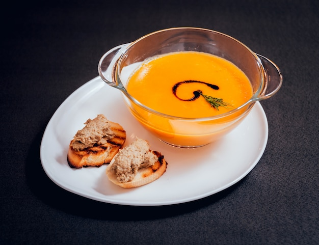 Pumpkin and carrot soup with cream and parsley on dark table
