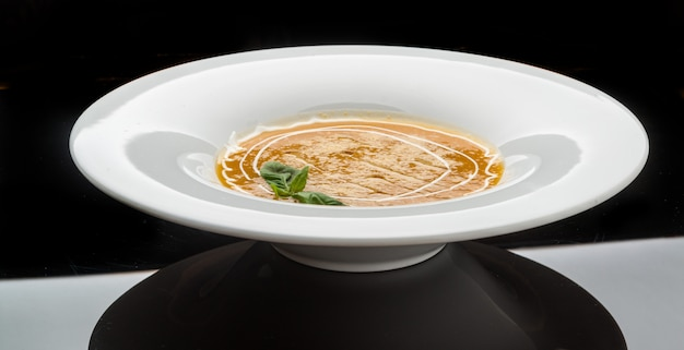 Pumpkin and carrot soup with cream and parsley on dark wooden surface top view