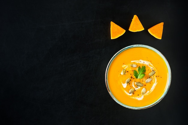 Pumpkin and carrot soup with cream, pumpkin seeds and parsley on dark scratched background.