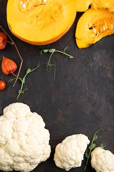 Pumpkin, cauliflower, pea sprouts on a black concrete background. top view, flat lay, copy space.
