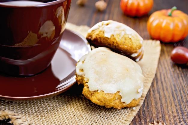 삼베, 호박, 나무 판자 배경에 도토리의 냅킨에 갈색 컵과 호박 쿠키
