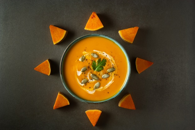 Pumpkin cream soup in a bowl decorated with pumpkin slices