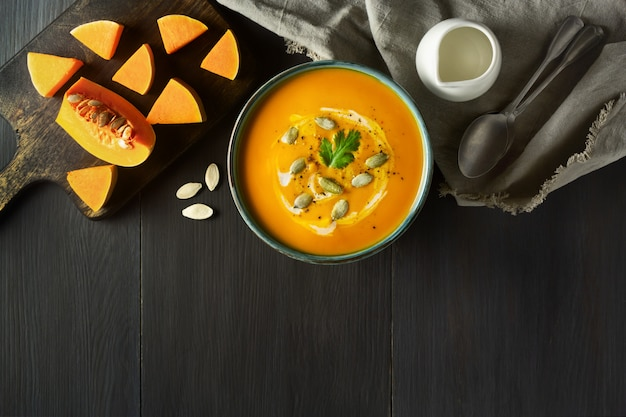 Pumpkin cream soup in a bowl with pumpkin seeds, parsley, cream and pumpkin slices on wooden table