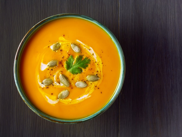 Pumpkin cream soup in a bowl with pumpkin seeds, parsley and cream on wooden table.