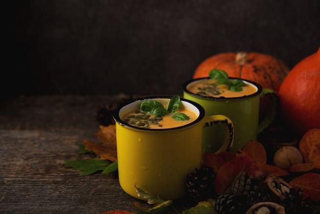 Тыквенный крем-суп в кружках, тыквы и опавшие листья на деревянном столе