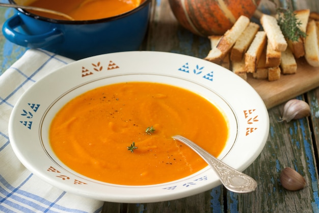 Pumpkin cream soup in a white plate on a wooden table