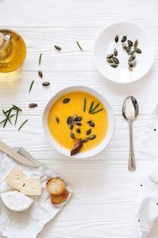 Тыквенный крем-суп с сыром и луком на белой доске. натюрморт плоская планировка