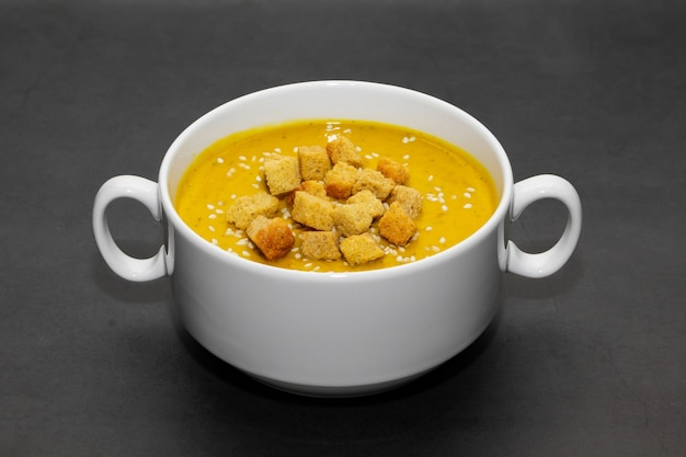 Pumpkin cream soup with crackers on a dark background. pumpkin cream soup with crackers and sesame seeds in a white bouillon on a dark background