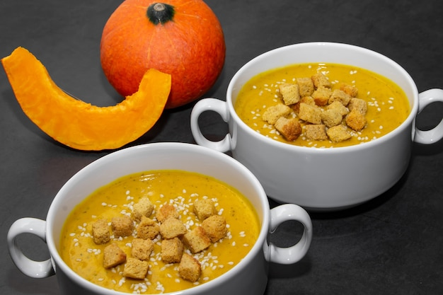 Pumpkin cream soup with crackers on a dark background. two bowls with pumpkin soup and crackers on a dark background