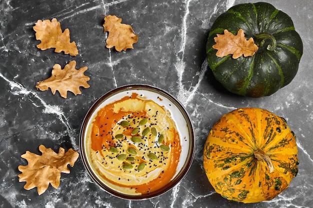 Тыквенный крем-суп со сливками и тыквой, семенами черного тмина и органическими декоративными тыквами с опавшими листьями дуба .. осенний натюрморт. вид сверху