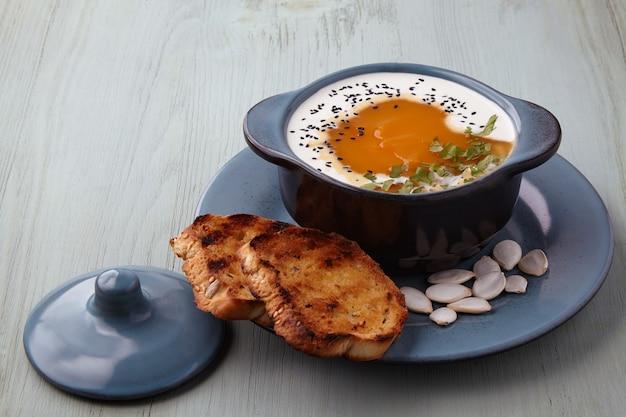 Тыквенный крем-суп со сливками черного тмина, зеленью и гренками