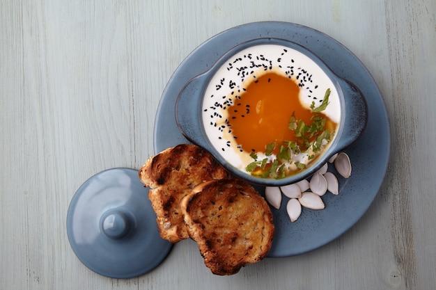 クリームブラッククミンシードハーブとトーストパンのカボチャクリームスープ
