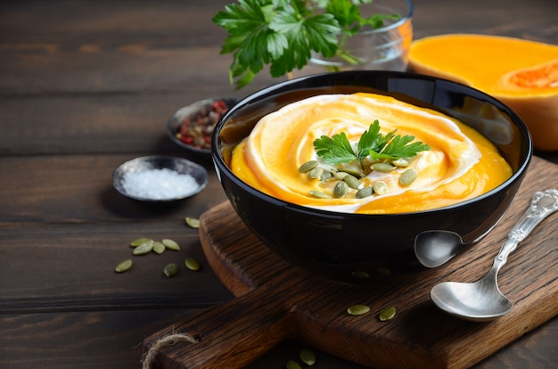 Pumpkin cream soup with cream and pumpkin seeds on wooden table.
