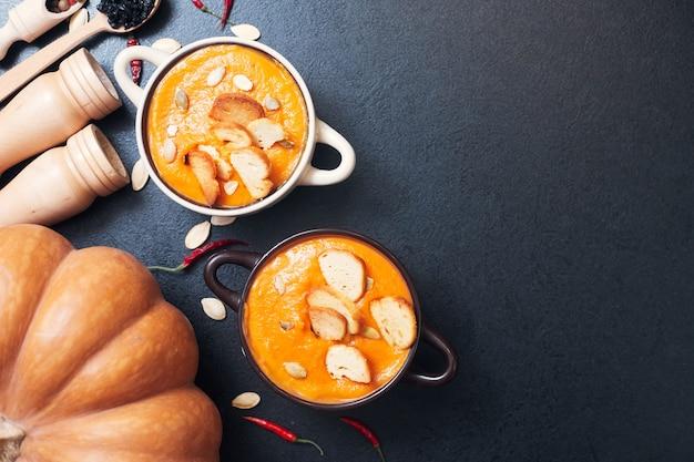 スパイスと黒いテーブルの上のクルトンとカボチャのクリームスープ。高品質の写真