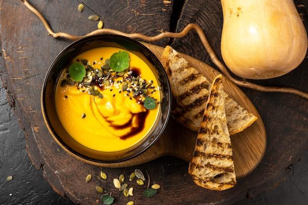 Тыквенный крем-суп с белым хлебом на гриле. тыквенные семечки, бальзамик, жареная киноа. диетическое веганское блюдо из отварных овощей