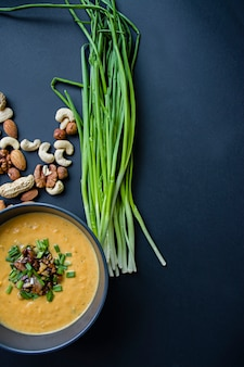 Pumpkin cream soup with herbs and nuts, served in a dark bowl.