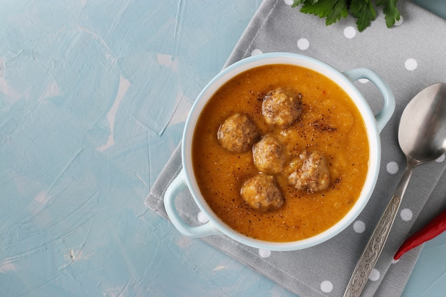 Pumpkin cream soup with meatballs in bowl on light blue wall, horizontal format, closeup
