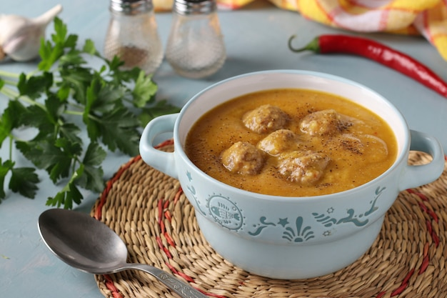 Pumpkin cream soup with meatballs in bowl on light blue wall, horizontal format