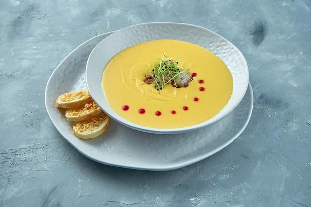 タコとクルトンの白いボウルのパンプキンクリームスープ。クリーミーなシーフードスープ