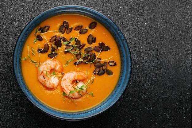 Тыквенный крем-суп с семенами и креветками на темном бетонном столе и вид сверху микрозелени