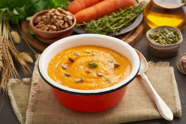 Тыквенный крем-суп из семян и грецких орехов, морковь, вид сбоку с осенними листьями для атмосферы