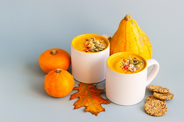 Pumpkin cream soup with seeds and cream in ceramic mug and multigrain healthy crackers.