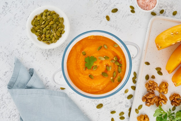 Pumpkin cream soup with seeds, top view light white background