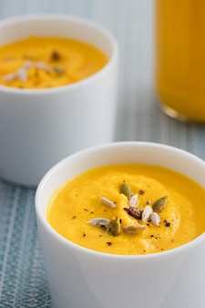 Pumpkin cream soup with seeds in two white bowls