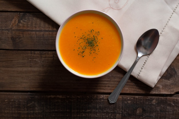 Pumpkin cream with chives and parsley on wooden table