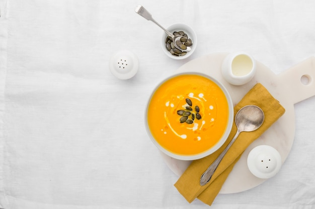 Pumpkin creamy soup decorated with fresh cream