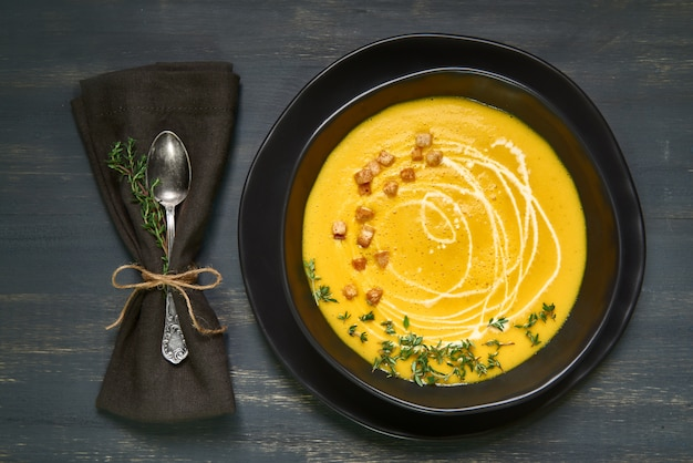 Pumpkin creme soup in black ceramic bowl on dark, flat lay