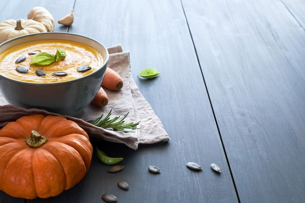Pumpkin creme soup with carrot, ginger and garlic on blue wood