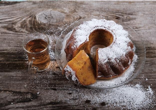 木製のテーブルに粉砂糖とカボチャのカップケーキ