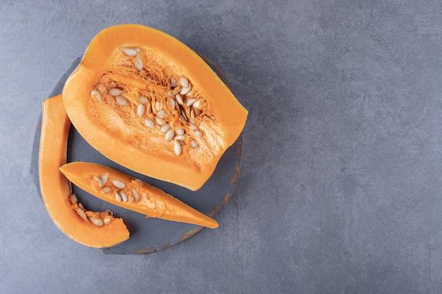 かぼちゃは、大理石の表面で、板の上で切り分けられます。