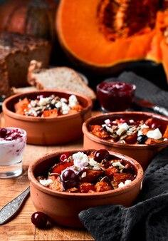 カボチャ料理。カボチャのスライスをオーブンで焼き、羊のチーズ、種子、クランベリーをベーキングディッシュに入れます。