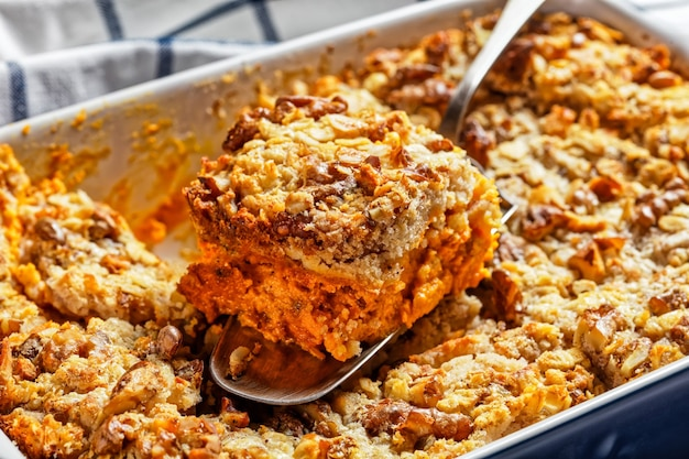 Pumpkin dump cake with traditional pumpkin pie spices: cinnamon, clove, nutmeg with walnuts and rolled oats on top served on a baking dish on white marble background, top view, close-up