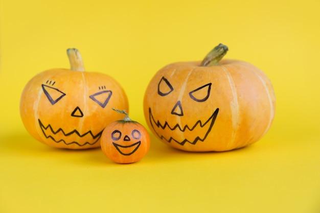 Семья тыквы с страшными злыми лицами на желтом фоне. концепция шаблона haloween.