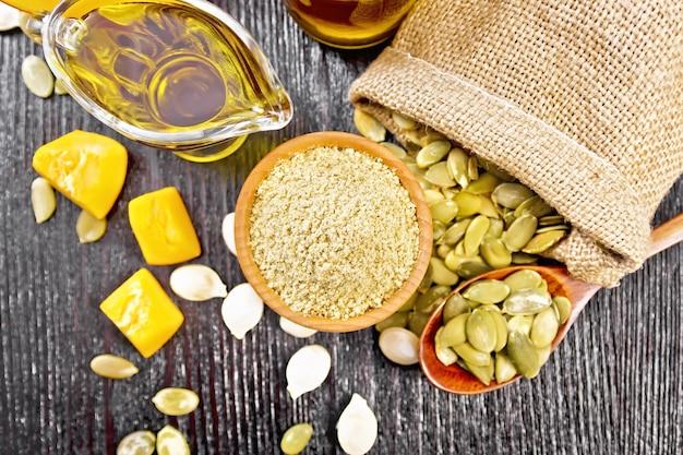 그릇에 호박 가루, 소스 보트와 항아리에 기름, 가방에 씨앗, 테이블과 숟가락에, 위에서부터 나무 판자 배경에 야채 조각