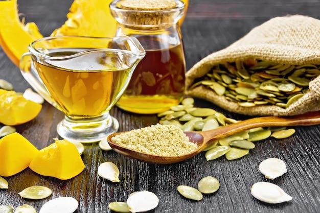 スプーンのカボチャ粉、グレイビーボートとジャーの油、バッグとテーブルの上の種子、野菜のスライス