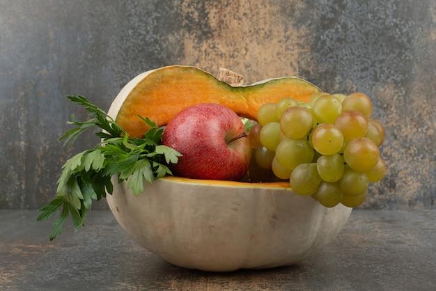 大理石の壁にリンゴとブドウでいっぱいのカボチャ