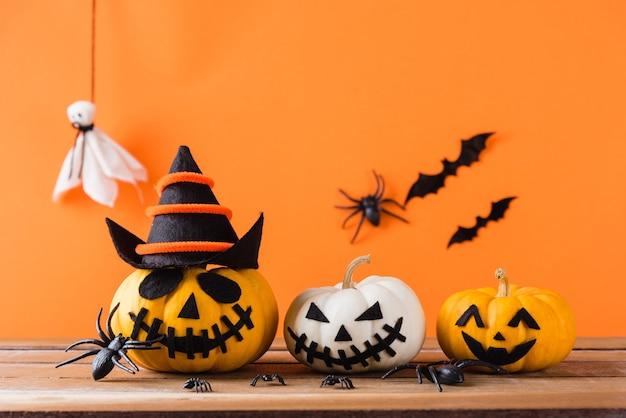 Тыква призрак страшный джек o фонарь лицо, черный паук и летучие мыши на деревянном столе