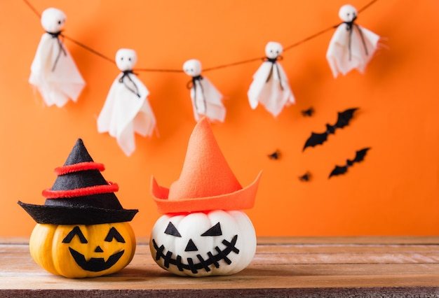 Тыквенный призрак жуткий джек о фонарь лицо носить шляпу, черный паук и летучие мыши на деревянном столе