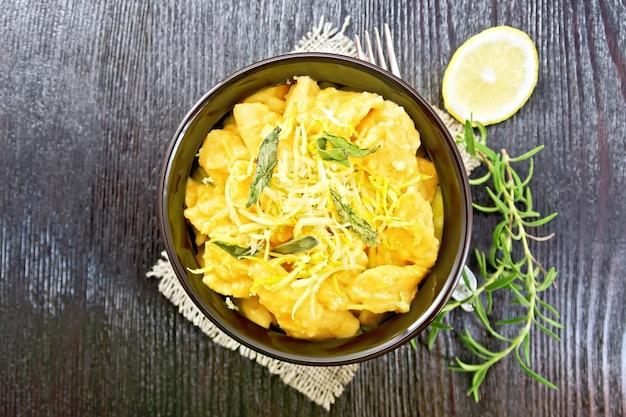 セージ、レモン、チーズ、バターを黄麻布のボウルに入れ、木の板を上に乗せたカボチャのニョッキ